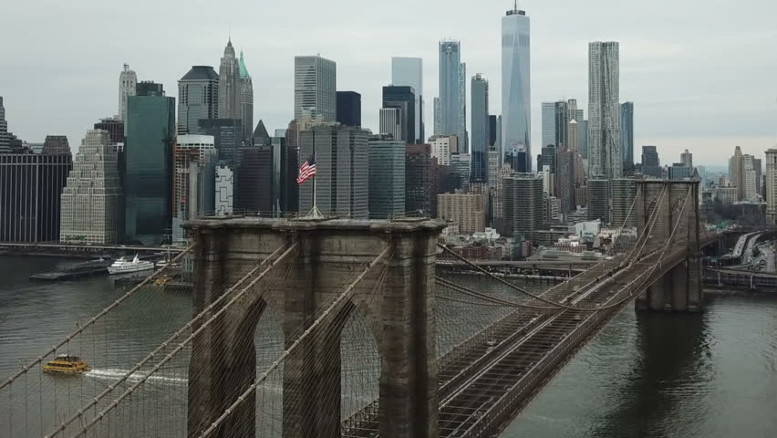 NEW YORK CITY - FEB 2, 2018: Brooklyn Bridge aerial over American flag toward Freedom Tower Manhattan skyline in NYC. The famous suspension bridge is one of the oldest roadway bridges in the US.