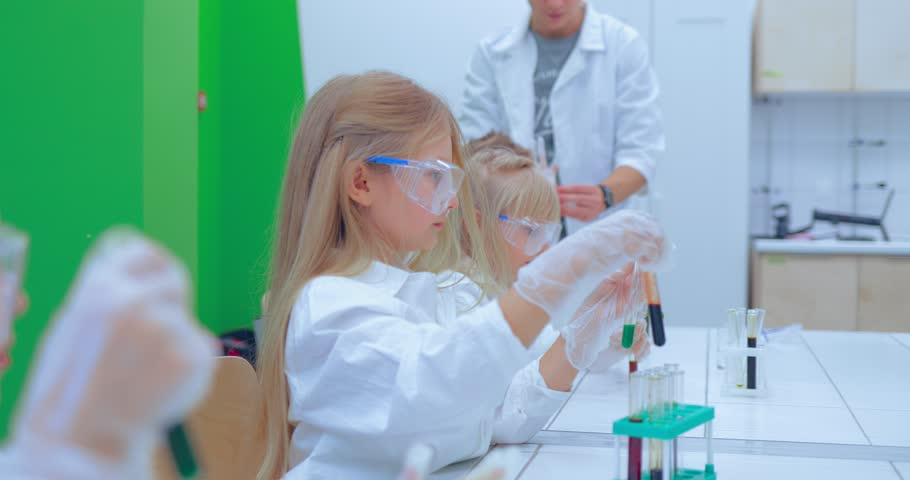 Teacher and students doing science experiment in school classroom. Children in chemistry class | Shutterstock HD Video #1007553382