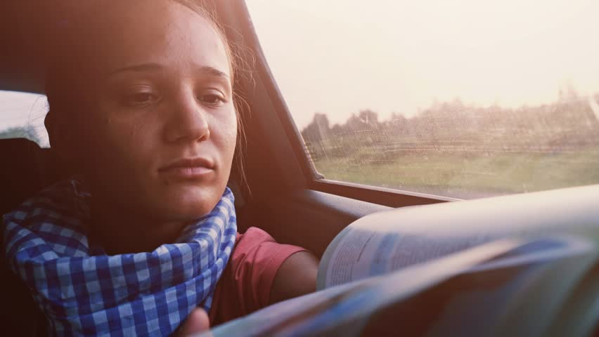 Pretty brunette woman reading a book while traveling in a car during beautiful sunset. 3840x2160