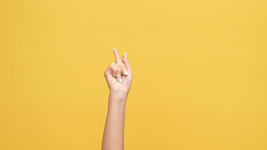 Woman hand pointing at someone over yellow background | Shutterstock HD Video #1007574775