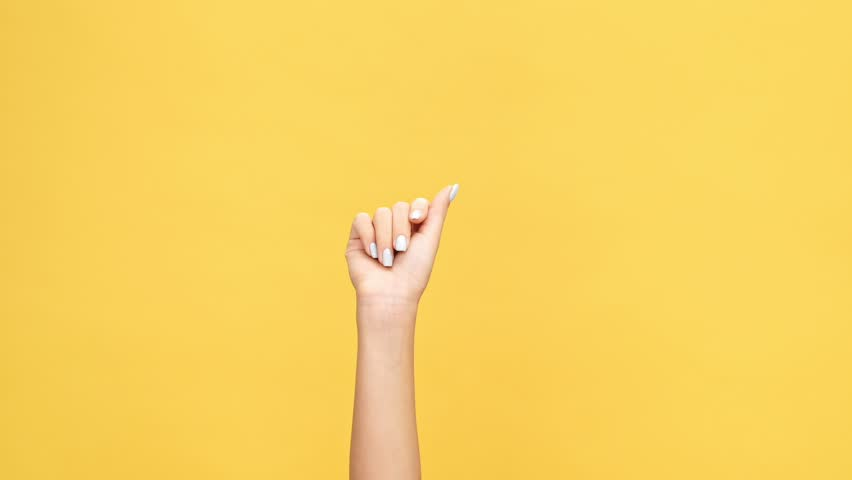 Woman hand snaps her fingers over yellow background