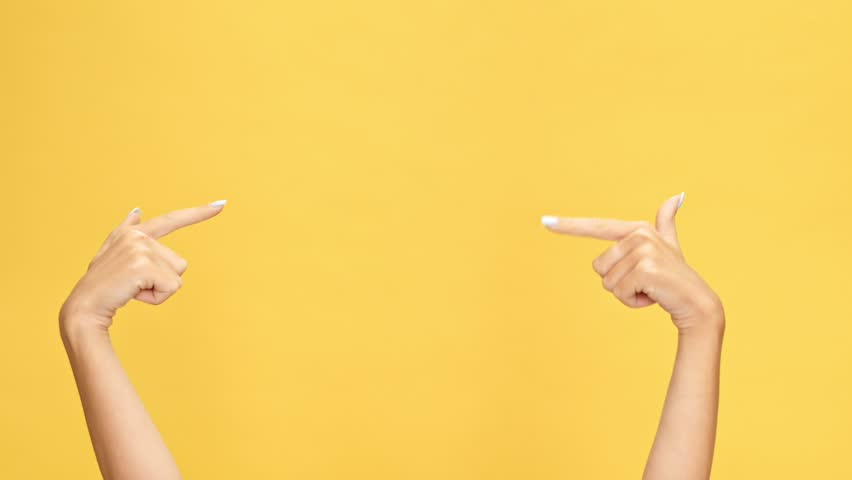 Woman hands pointing on copyspace and showing thumbs up over yellow background