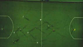 Aerial football match play. Clip. Aerial shot Two teams playing ball in football outdoors, top view. Football game outdoors, green field with markings, players running around with a ball