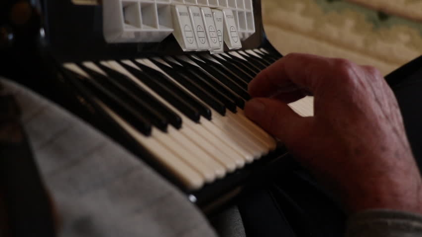 Musician playing the accordion close up. Hands playing music on a key board shot over the shoulder. Man plays an accordion as a hobby for enjoyment.