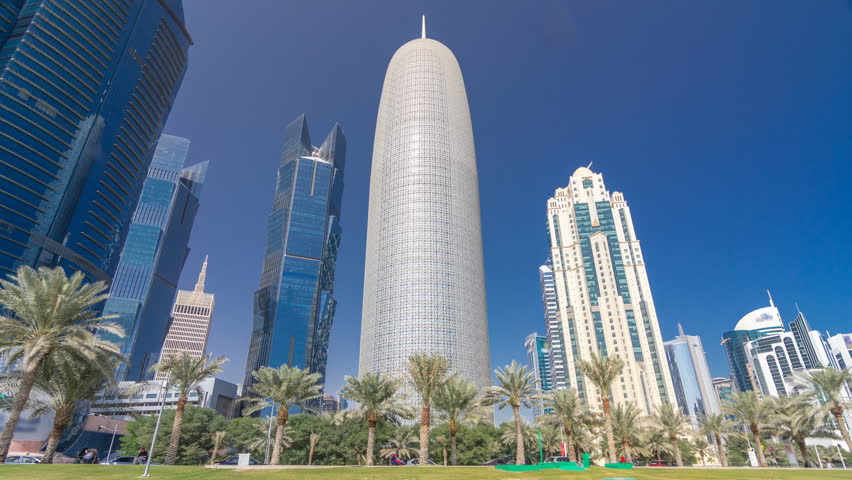 The skyline of Doha seen from Park timelapse hyperlapse, Qatar. Trees and palms on foreground. Mordern skyscrapers and towers on background. Traffic on road