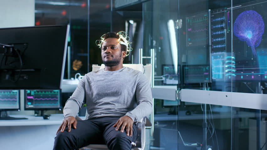Man Wearing Brainwave Scanning Headset Sits in a Chair while Watching Stimulating Images on Display. In the Modern Brain Study Laboratory Monitors Show EEG Shot on RED EPIC-W 8K Helium Cinema Camera. | Shutterstock HD Video #1007612581