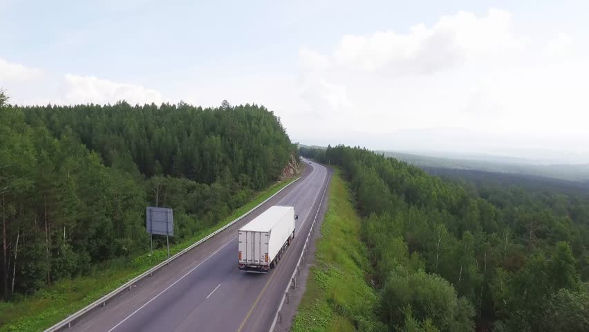 One white truck driving along the freeway amidst a dense forest in the mountains. Summer, sunny, beautiful sky with clouds. Aerial drone view. | Shutterstock HD Video #1007618764