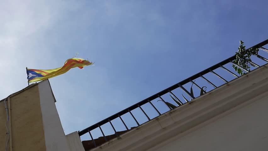 Catalonia red and yellow flag with star waves on house top under blue sky on sunny day, slow motion | Shutterstock HD Video #1007625613