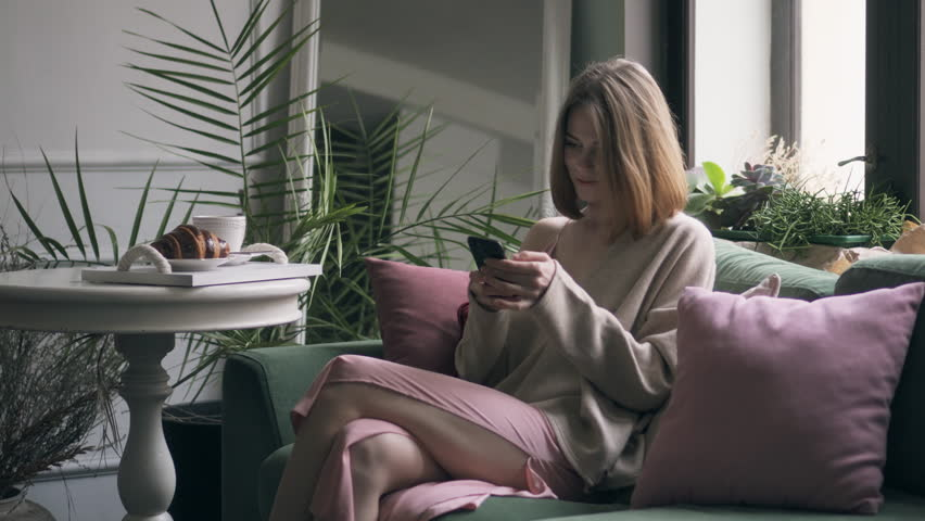 Carefree woman drinking coffee and using mobile phone | Shutterstock HD Video #1007626327