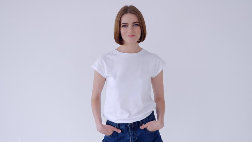 Beautiful woman folded arms while posing in jeans shorts and white T-shirt | Shutterstock HD Video #1007626501