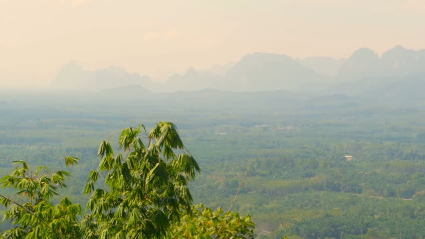 View of the valley with mountains in the background. Pointed rocks on the horizon. Green forests onthe plain. Typical Asian Landscape. Virgin nature of the southeast asia. Thailand.