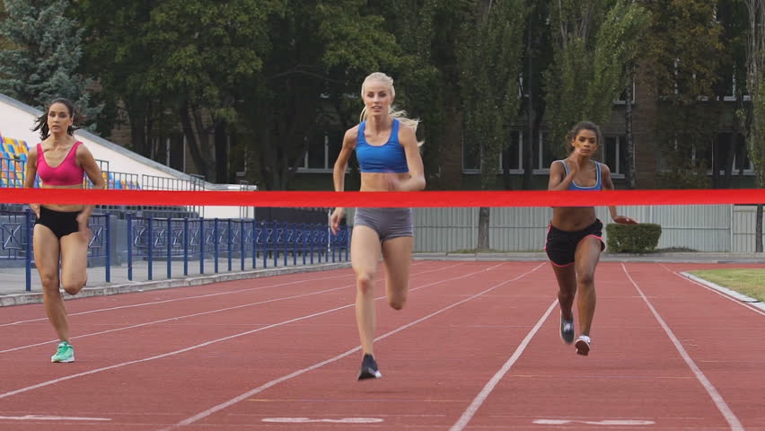 Female marathon runners crossing finishing line on professional sports arena. Fitness women racing competition at stadium, victory celebration, achievement. Motivated blond girl winning speed contest