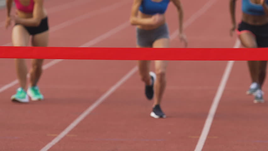 Young athletes running on stadium, crossing finishing line in slow-motion