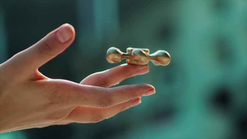 Close up shot of female's hand keeping golden fidget spinnet in her hand. Spinner slowly rolling on her finger. | Shutterstock HD Video #1007646805