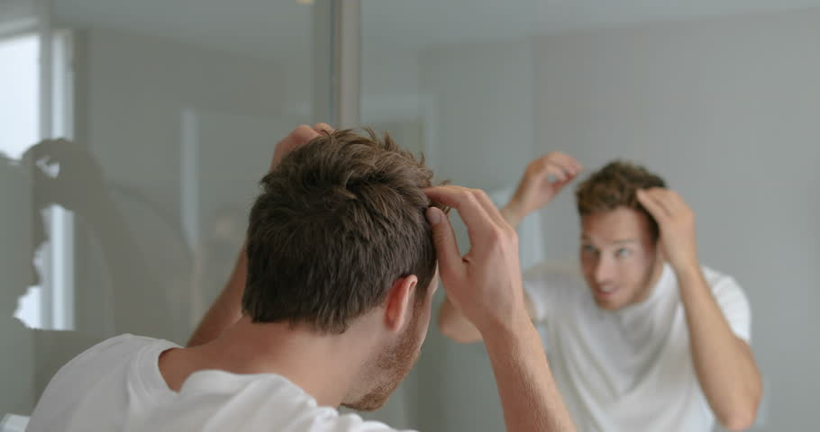 Man looking in bathroom mirror putting wax product touching his hair styling or checking for hair loss problem. Male problem of losing hairs.