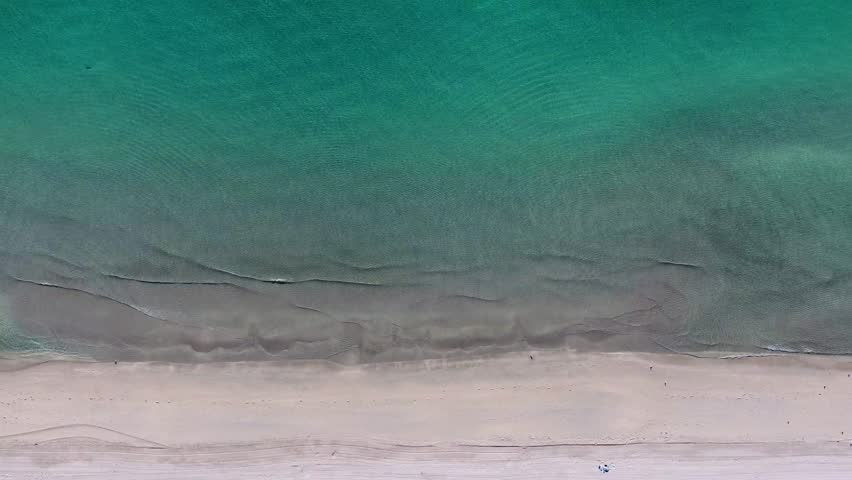 Tropical beach ocean waters filmed in a seamless infinite footage video loop shows crystal clear green water and white sand beach with bird flying while calm waves seen from overhead bird eye view | Shutterstock HD Video #1007651248