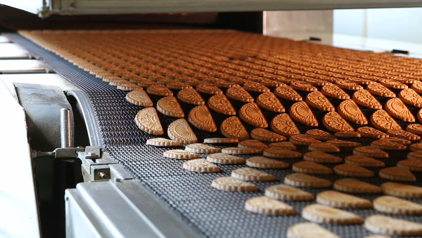 Production line of baking cookies. Conveyor with cookies. Many sweet cake food factory. Freshly baked shortbread cookies leave the oven. Cookies on a conveyor in a confectionery factory oven. Royalty-Free Stock Footage #1007652484