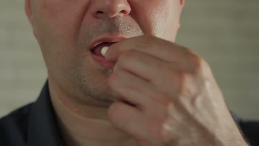 Closeup of a man ingesting a pill and drinking it with a glass of water
