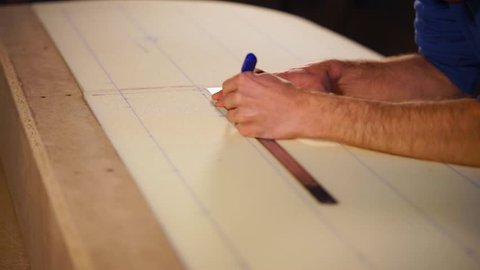Master is making marks on detail of subject of furniture. He is measuring with metal ruler and drawing with pen