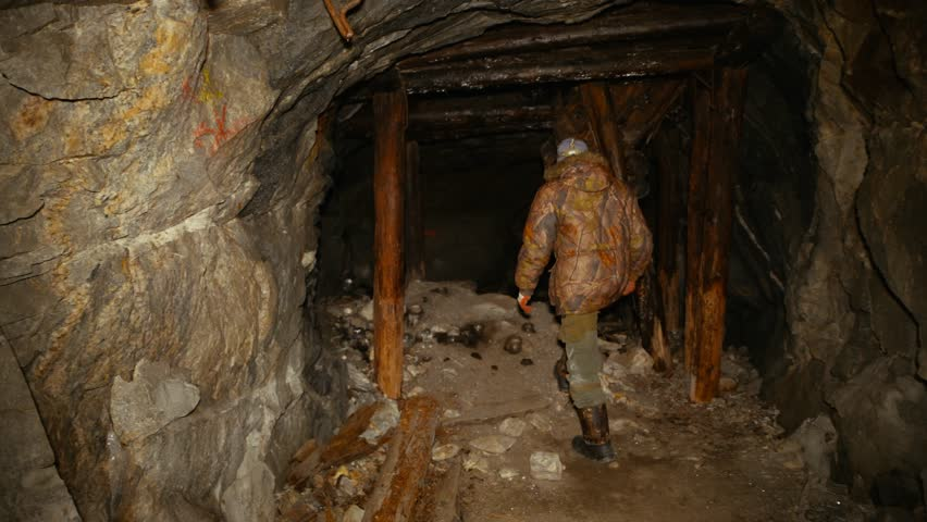 A man in the dark with a flashlight is walking along an abandoned mine with wooden supports | Shutterstock HD Video #1007682709