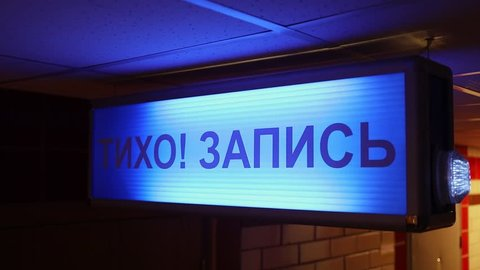 Sign board with blinkers and russian inscription QUIET! RECORDING