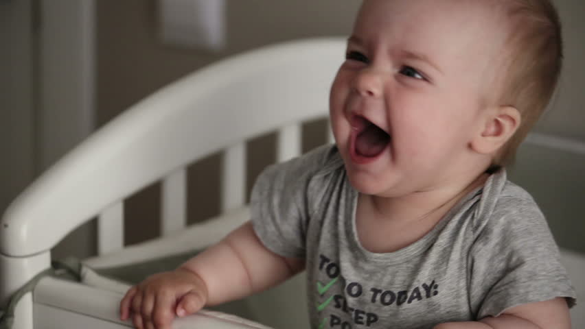 Baby girl laughing and having fun in crib. Happy baby. Baby emotions. Baby smile.