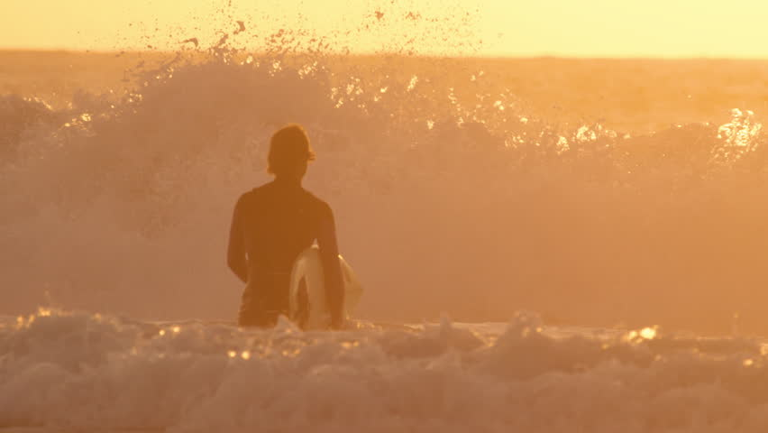 SLOW MOTION: Large ocean waves violently crash and break in front of golden lit surfer. Unrecognizable male surfer walks towards ocean waves with surfboard in his hand on a beautiful golden evening.