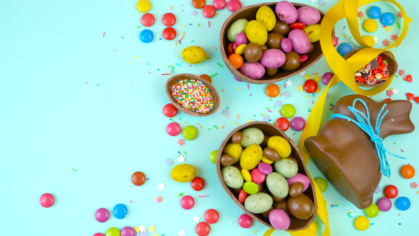Happy Easter decadent chocolate background overhead with Easter eggs and candy on a rustic wood background with copy space. | Shutterstock HD Video #1007694799
