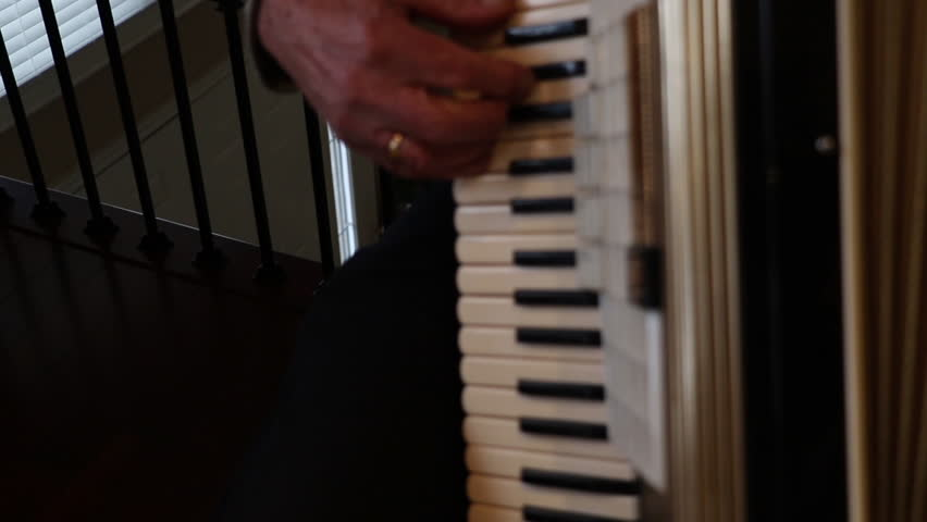Playing the accordion close up. Musical instrument being played by an older man. Accordion keys being played. People playing musical instruments.