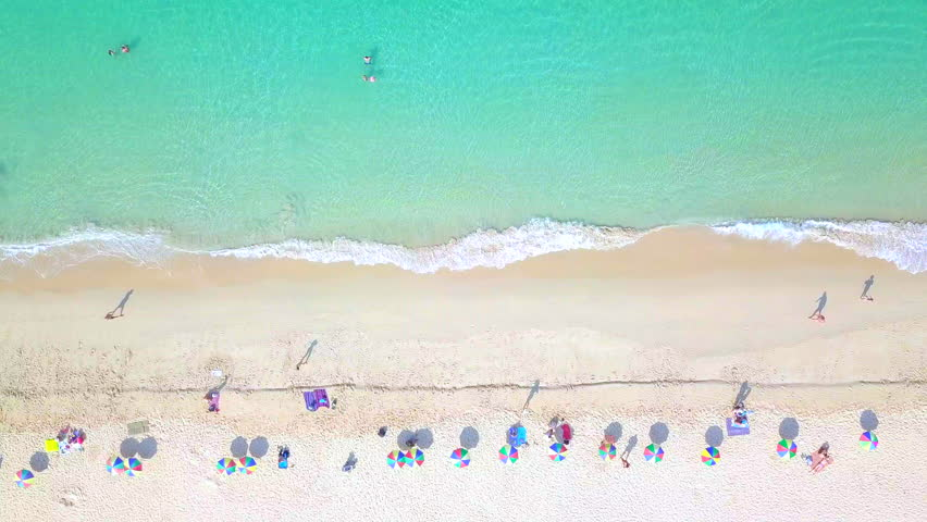 Aerial top view crowd people at Surin Beach in Phuket, Thailand, Southern beach of Thailand, Surin beach is very beautiful famous tourist destination in Andaman sea, Phuket, 4k aerial view beach.