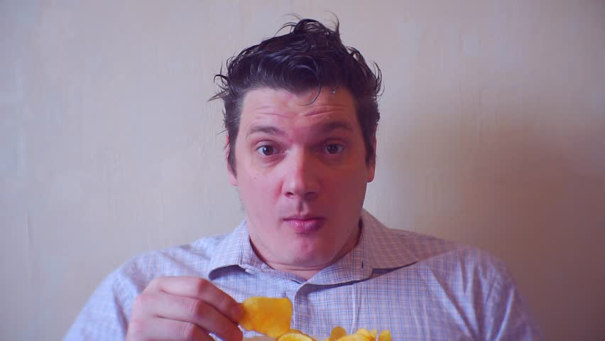 Portrait of a crazy man, carefully looking at the camera and eats chips | Shutterstock HD Video #1007700541