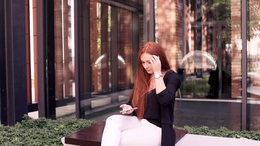 Young pretty woman with red hair texting on smartphone on the bench | Shutterstock HD Video #1007703532
