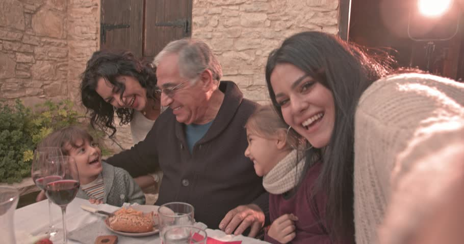 Family video-calling using smartphone during lunch at traditional village house in Italy
