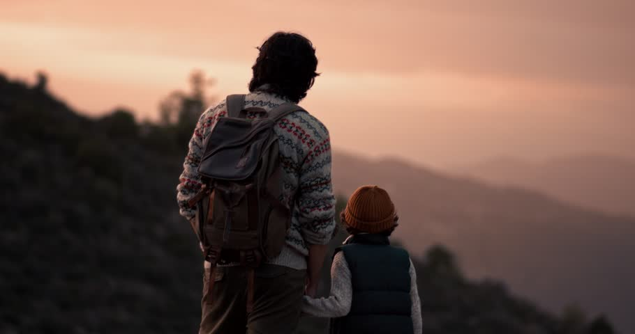 Young father and son hiking on mountain, standing on mountain peak and looking at view