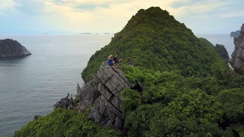 HA LONG, CAT BA/VIETNAM - AUGUST 18 2017: Drone removes from tourists sitting on large steep hill stone top to sand beach at mountain foot against endless bay on August 18 in Ha Long