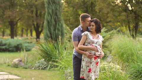 A pregnant woman and her husband walking in summer Park at sunset. Slow motion. Happy family expecting a baby.