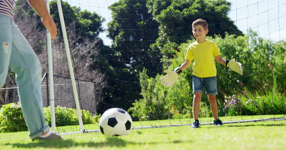 Father and son playing football in park   Shutterstock HD Video #1007725591