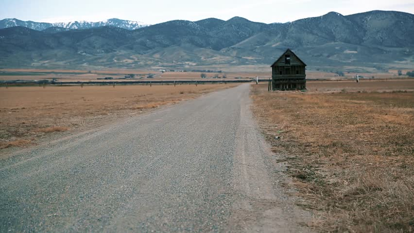 Tumbleweed along the road of a ghost town, abandoned house in background Royalty-Free Stock Footage #1007729269