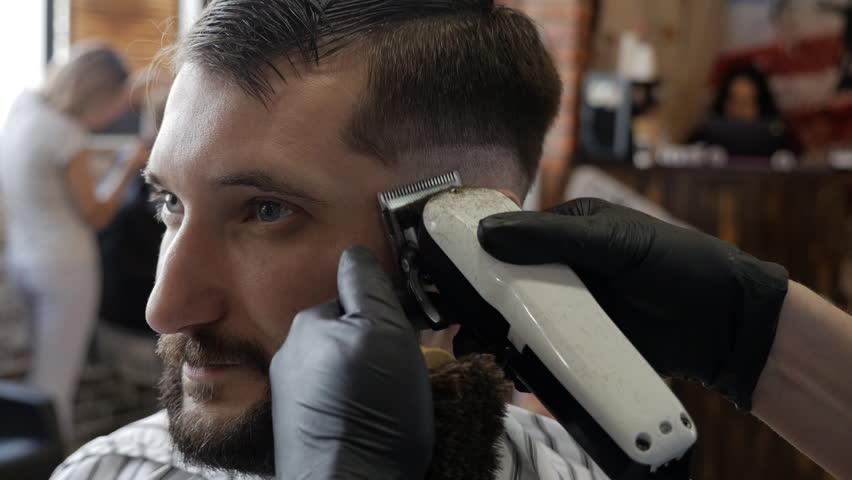 Man hands grooming man hair in barber shop #1007741755