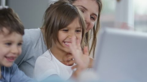 Mother and two preschool children using laptop computer for online communication, laughing and greeting someone they see on the screen