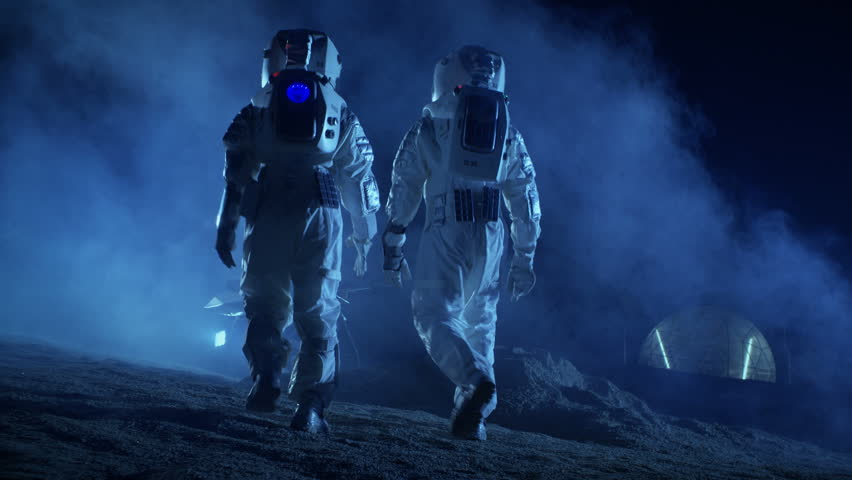 Following Shot of Two Astronauts in Space Suits on Alien Planet Walking Toward Rover and Geodesic Dome. High-Tech Space Exploration Concept. Shot on RED EPIC-W 8K Helium Cinema Camera.