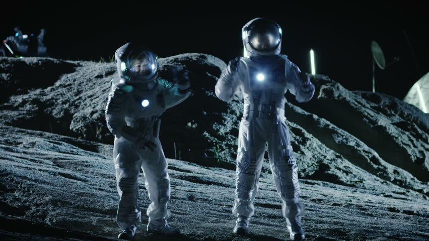 Male and Female Astronauts Wearing Space Suits Dance on the Surface of the Alien Planet. Humanity Colonizing Space Celebration Theme. Shot on RED EPIC-W 8K Helium Cinema Camera. Royalty-Free Stock Footage #1007756950