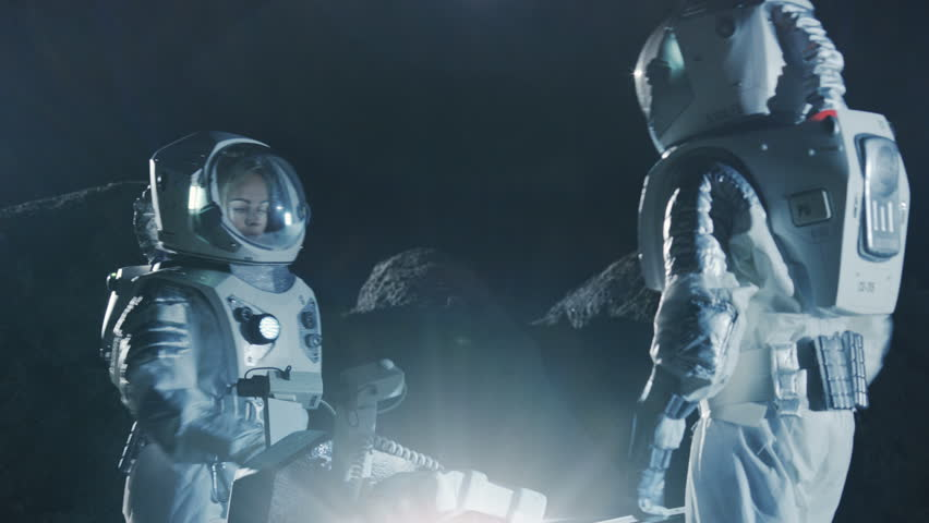 Two Astronauts in Space Suits on an Alien Planet Prepare Space Rover for Surface Exploration Mission. Futuristic Concept about Space Travel and Colonization. Shot on RED EPIC-W 8K Helium Cinema Camera