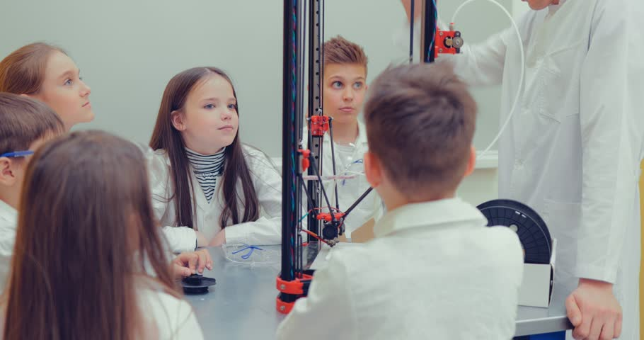 Schoolboy and schoolgirls in the classroom creating models for project using 3D printer