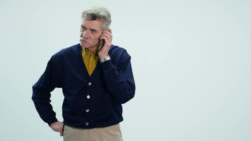 Senior business man shocked over the news he receives on his cell phone, white background