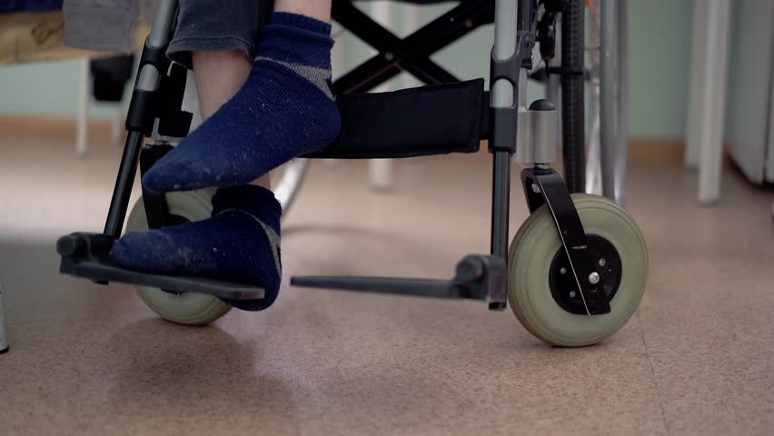 Close-up, low angle shot disabled young guy with spinal cord and leg problems (multiple sclerosis) puts feet on wheelchair footrest   Shutterstock HD Video #1007776846