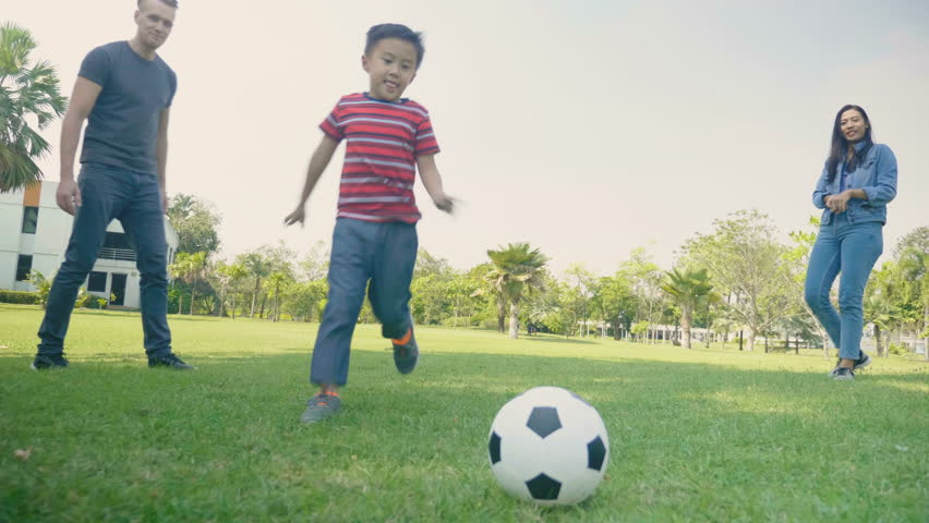 Child playing football game with parents in park. Slow motion.   Shutterstock HD Video #1007799112