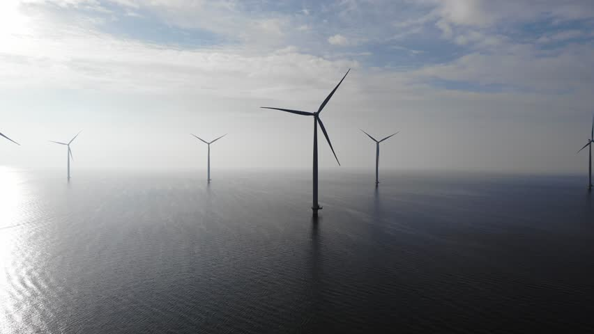 Offshore Windmill farm in the ocean  Westermeerwind park , windmills isolated at sea on a beautiful bright day Netherlands Flevoland Noordoostpolder, drone view bird eye view of windmill farm Royalty-Free Stock Footage #1007804668