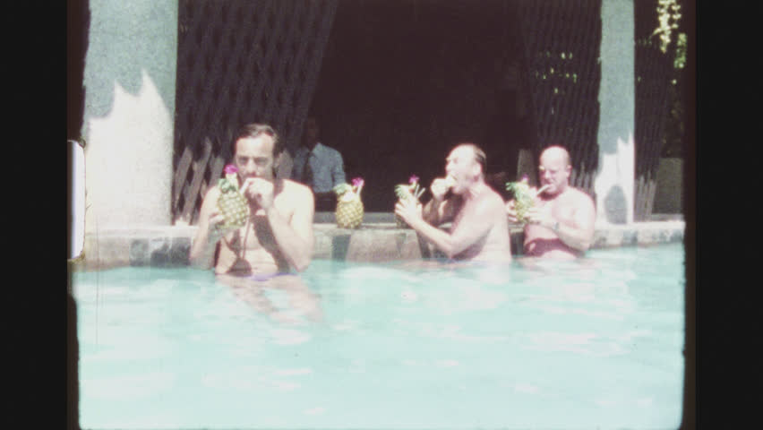 PATTAYA, THAILAND, MAY 1978. Three Caucasian Bare Chested Male Tourists Hanging Out In A Hotel Pool, Enjoying A Cocktail Served In A Fresh Pinapple.