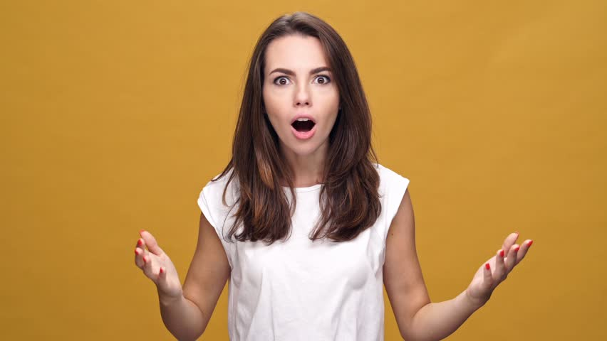 Young shocked surprised woman standing isolated over yellow background while looking camera Royalty-Free Stock Footage #1007831551